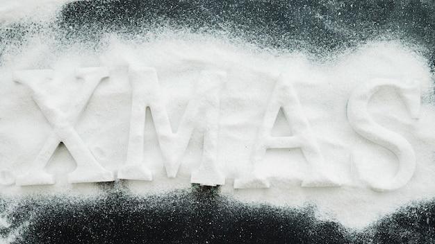 Xmas inscription between decorative snow Free Photo