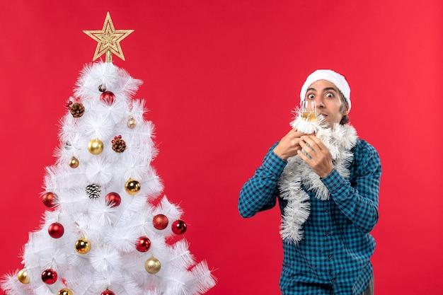 Рождественское настроение с молодым человеком в шапке санта-клауса и поднимающим бокал вина подбадривает себя возле елки Бесплатные Фотографии