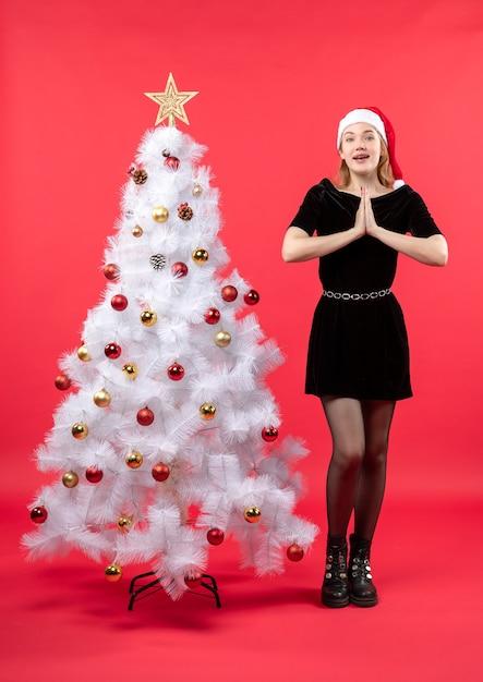 Рождественское настроение с молодой женщиной в черном платье и шляпе санта-клауса, стоящей возле белой елки и делающей жест благодарности Бесплатные Фотографии