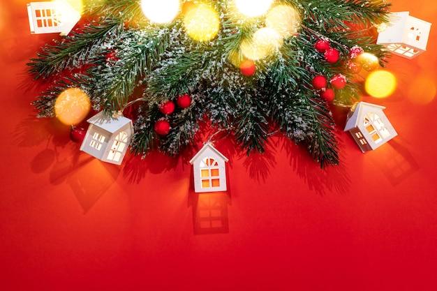 Рождественский красный фон с заснеженными еловыми ветками, светящимися рождественскими огнями, белыми домиками с красивыми тенями и золотыми огнями боке. уютное рождество дома концепции. вид сверху. скопируйте пространство. Premium Фотографии