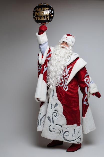 お祝いの幸せな新年の風船とサンタの衣装でクリスマスシニア男性 無料写真