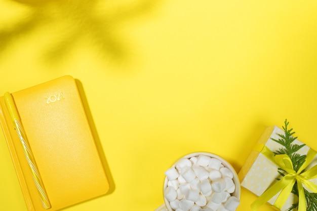 Xmas концепция рабочего пространства в желтом цвете. блокнот-органайзер на 2021 год, чашка кофе с зефиром, подарочная коробка своими руками, тени еловых веток на желтом. подведение итогов, планирование. вид сверху, плоская планировка, копия пространства. Premium Фотографии