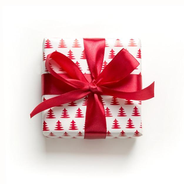 Рождественский подарок с красным бантом на белом. xmas. счастливый. новый год. стиль плоской планировки. Premium Фотографии