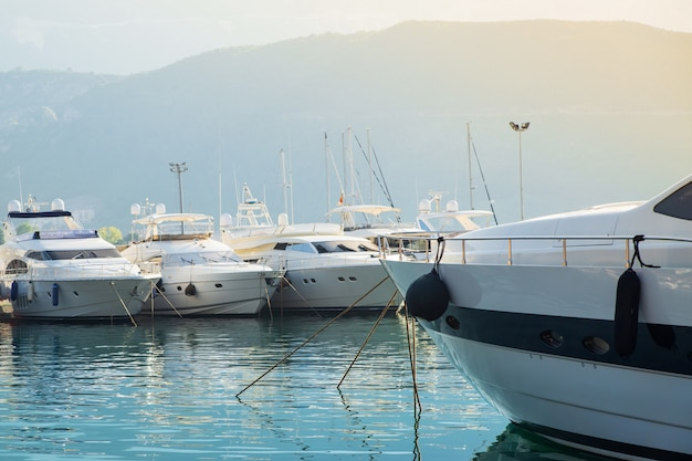 Yacht on the background of boat port and mountain in the sun Premium Photo