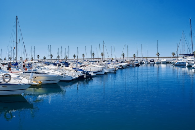 Yacht harbor in blue sunset light, luxury summer cruise, leisure time, active life, vacation and holidays concept yachts and their reflection in the city's port. Premium Photo