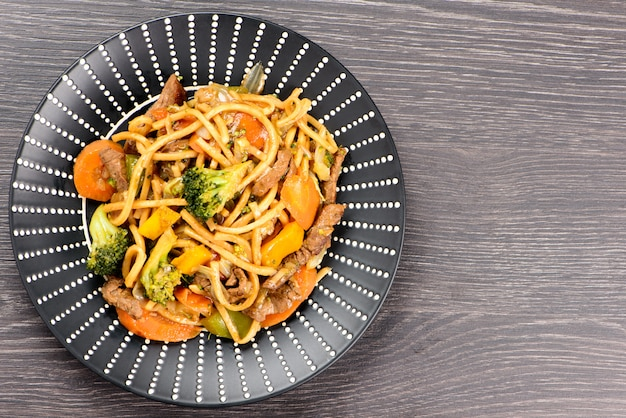Yakisoba on a black plate on a table Premium Photo
