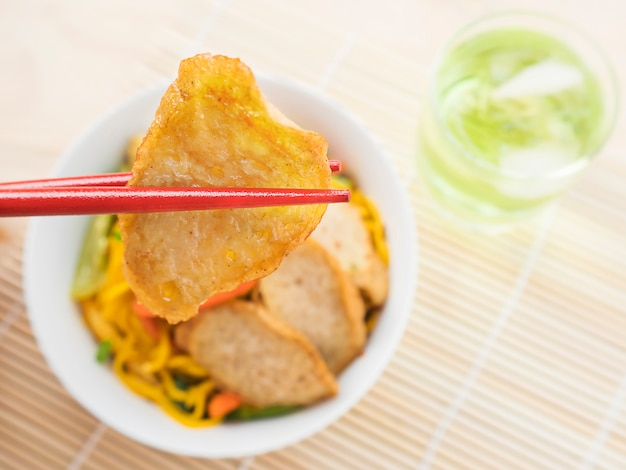 Yakisoba with chopstick and hand over bamboo pad Free Photo