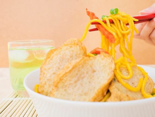 Yakisoba with glass of cold green tea over bamboo pad with chopstick and hand Free Photo