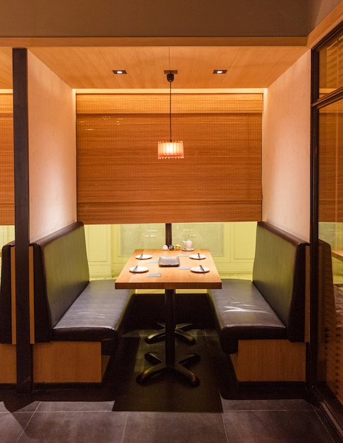Yakitori japanese grilled skewer restaurant private seating area. mostly decorated with oak wood texture. minimalist interior design. Premium Photo