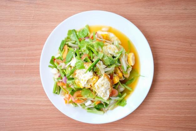 Пряный салат с яичницей (yam kai dao) служит на белом блюде установленном на коричневую таблицу - домодельную концепцию еды. Premium Фотографии