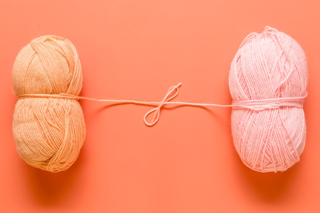 Yarn for knitting tied in bow on orange background Free Photo