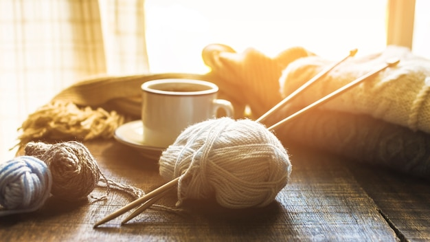 Yarn and needles near hot beverage Free Photo