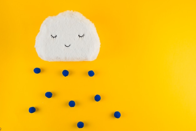 Yarn white clouds with blue raindrops on yellow backdrop Free Photo