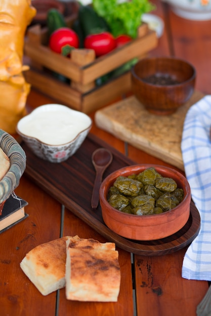 Yarpag dolmasi, yaprak sarmasi, green grape leaves stuffed with rice and meat in pottery bowl with yogurt. Free Photo