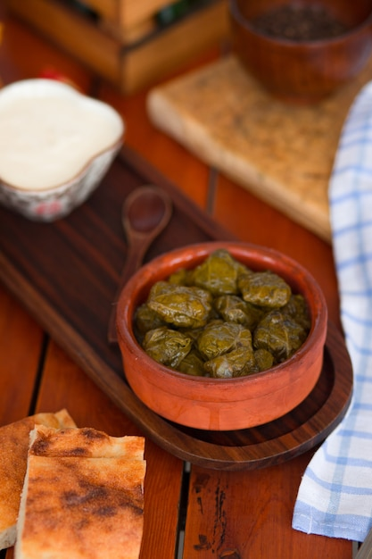 Yarpag dolmasi, yaprak sarmasi, green grape leaves stuffed with rice and meat in pottery bowl. Free Photo