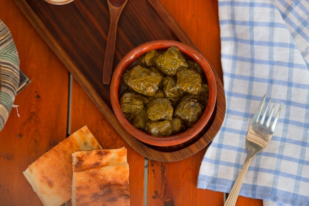 Yarpag dolmasi, yaprak sarmasi, green grape leaves stuffed with rice and meat in pottery bowl Free Photo