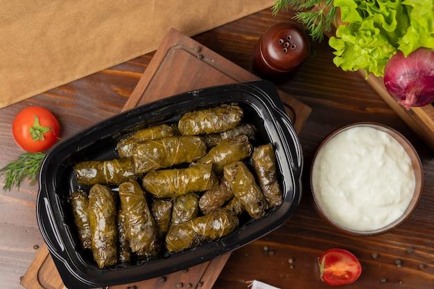 Yarpaq dolmasi, yaprak sarmasi, green grape leaves stuffed with meat takeaway Free Photo