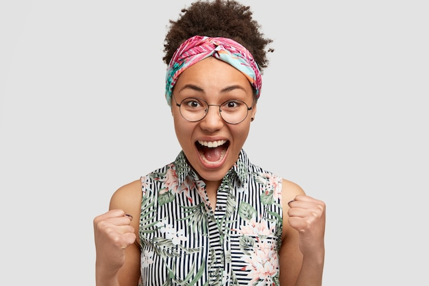 Yeah, that`s wonderfull! shot of glad african american female with crisp hair, screams with happiness, clenches fists, makes winning gesture, achieves everything in life, wears elegant blouse Free Photo