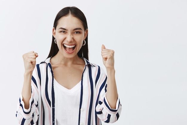 Yeah we did it. triumphing happy enthusiastic woman in striped blouse, lifting clenched fist and saying yes while celebrating successful deal or victory, being pleased and thrilled over gray wall Free Photo