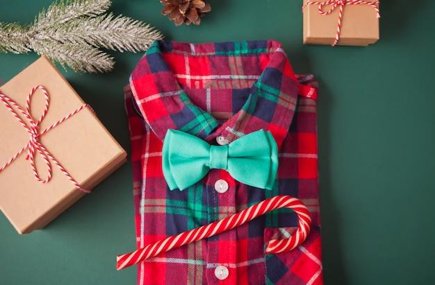 赤い格子縞のシャツ、蝶ネクタイ、キャンディケイン、ギフトボックス、緑のクリスマスデコレーション。大year日。クリスマスのファッション。 Premium写真