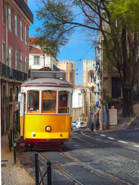 Yellow 28 tram in alfama, lisbon, portugal Premium Photo