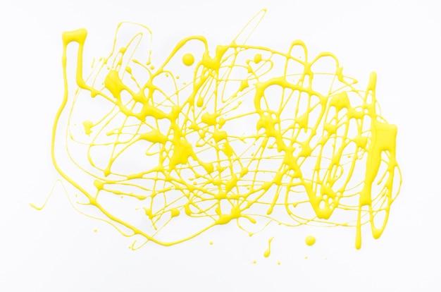 Yellow acrylic splash on white canvas Free Photo