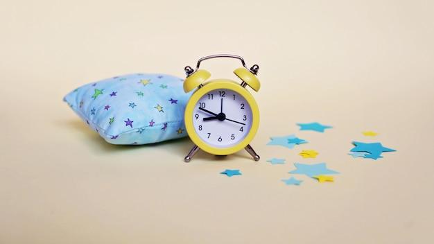 Yellow alarm clock and light blue pillow Premium Photo