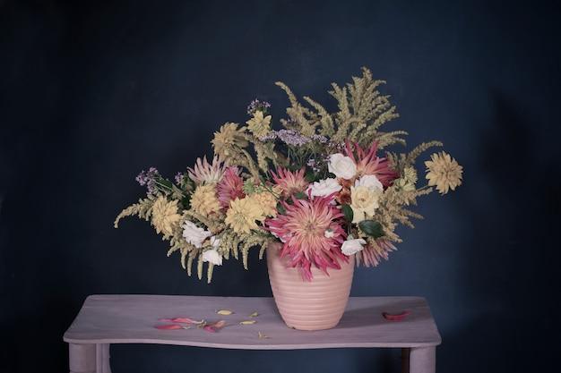 빈티지 선반에 꽃병에 노란색과 빨간색 꽃 프리미엄 사진