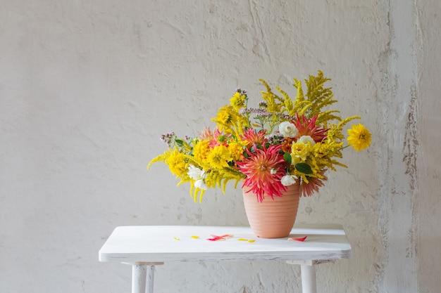 ヴィンテージ棚の花瓶に黄色と赤の花 Premium写真