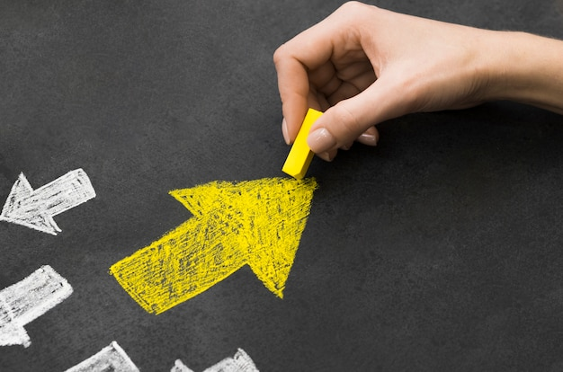 Yellow arrow in group of white arrows on black background Free Photo