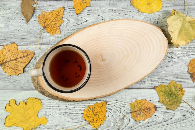 Yellow autumn leaves, a cup of tea on an old wooden background Premium Photo