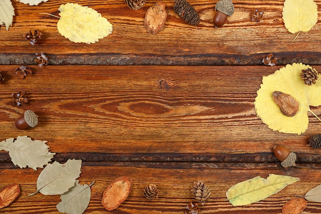 Yellow autumn leaves on a dark old wooden background with a blank space for text Premium Photo
