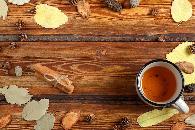 Yellow autumn leaves and a glass of tea on a dark old wooden background with a blank space for text Premium Photo