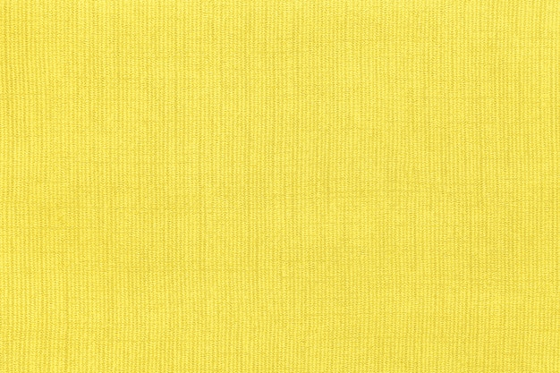 Yellow background from a textile material with pattern, closeup. structure of the fabric with natural texture. Premium Photo