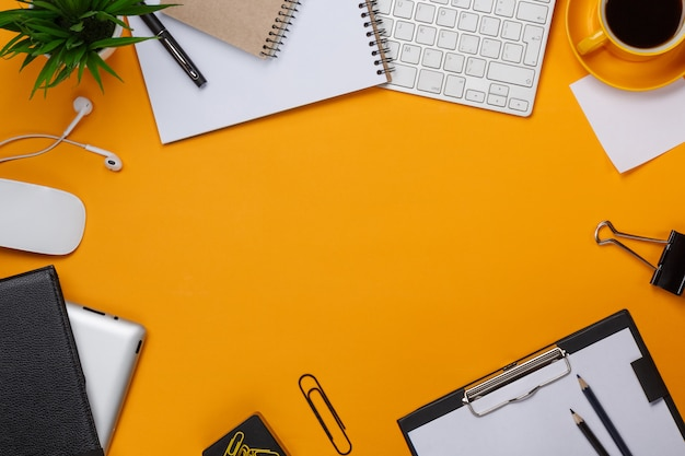 Yellow background mess on your desktop keyboard mouse cup of coffee business Premium Photo