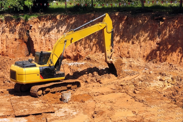 A yellow backhoe is working in the construction site Premium Photo