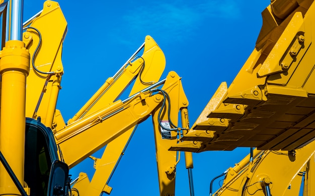 Yellow backhoe with hydraulic piston arm against clear blue sky. Premium Photo
