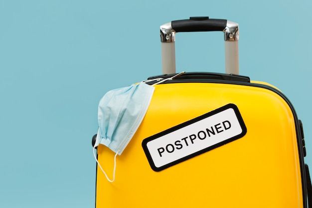 Yellow baggage with postponed sign and medical mask Free Photo