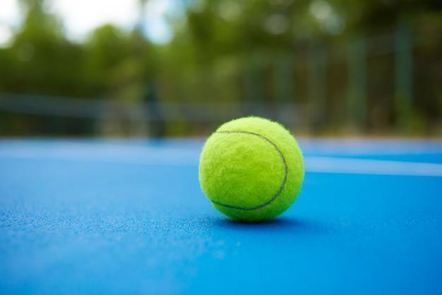La palla gialla sta ponendo sul tappeto blu del campo da tennis. piantagioni verdi vaghe e alberi dietro. Foto Gratuite