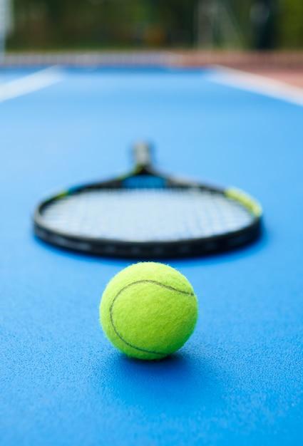 Желтый мяч лежит на синем ковре теннисного корта с профессиональной ракеткой. Бесплатные Фотографии