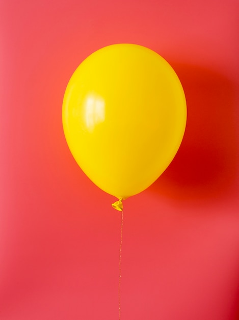 Yellow balloon on red background Free Photo