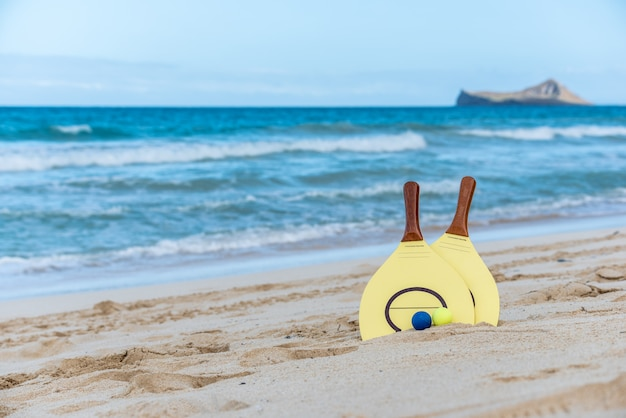 Yellow beach paddle and balls on a sandy beach in hawaii with waves and an island in the background Premium Photo