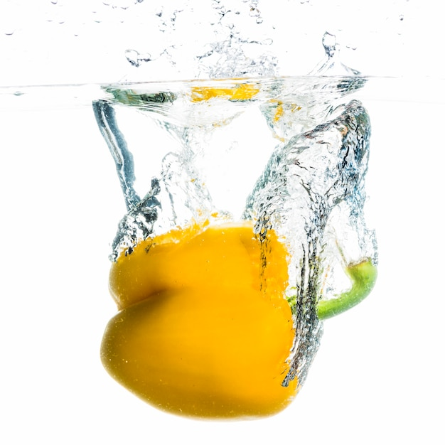 Yellow bell pepper splashing into the water against white background Free Photo