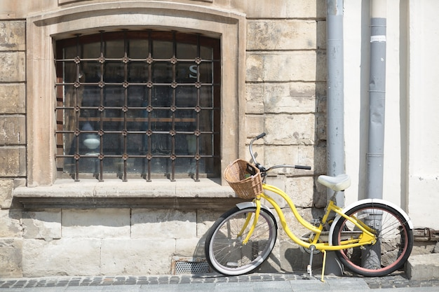 Yellow bicycle with basket in front of old wall Free Photo