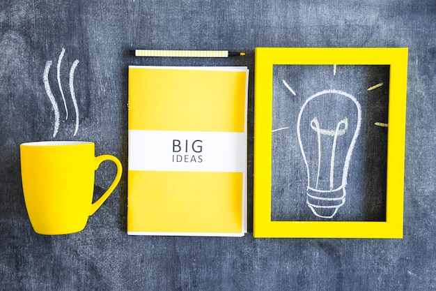 Yellow big ideas book; light bulb frame and coffee mug on chalkboard Free Photo