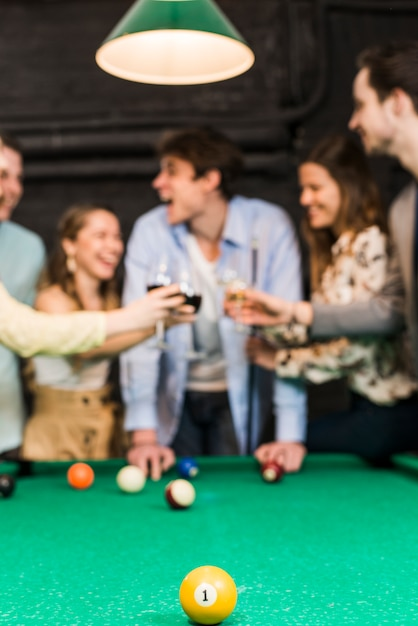 Yellow billiard ball with one number on snooker table in front of friends toasting wine Free Photo