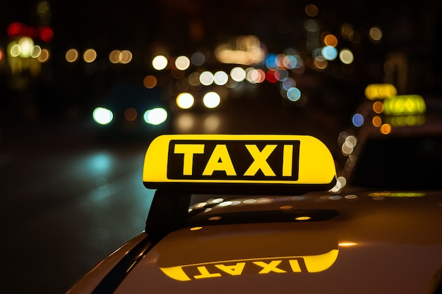 Yellow and black sign of taxi placed on top of a car at night Free Photo