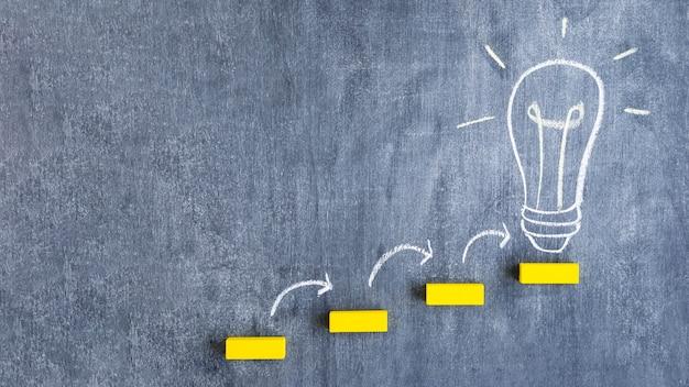 Желтый шаг блока на лампочке, нарисованной на доске Premium Фотографии