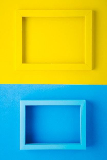 Yellow and blue frames on bicolor background Free Photo
