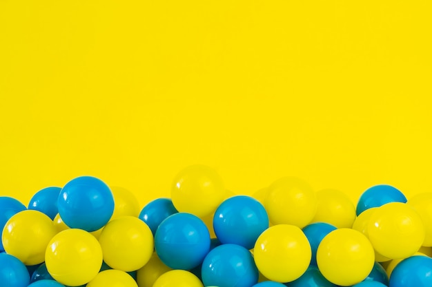 Yellow and blue plastic balls in pool of game room Premium Photo